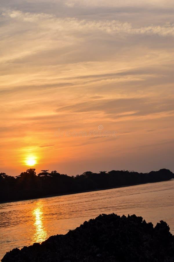 El cielo anaranjado sobre él con la reflexión de oro del sol impresionante en calma agita como fondo Opinión asombrosa de la pues imagen de archivo libre de regalías