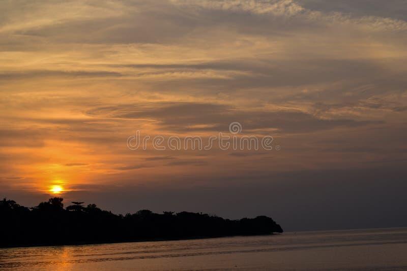 El cielo anaranjado sobre él con la reflexión de oro del sol impresionante en calma agita como fondo Opinión asombrosa de la pues fotos de archivo