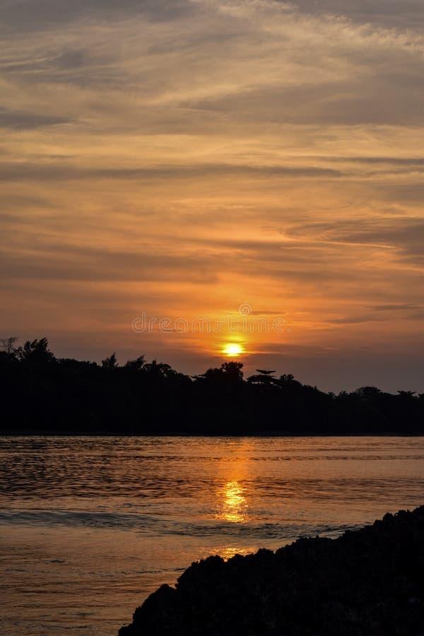 El cielo anaranjado sobre él con la reflexión de oro del sol impresionante en calma agita como fondo Opinión asombrosa de la pues fotografía de archivo libre de regalías