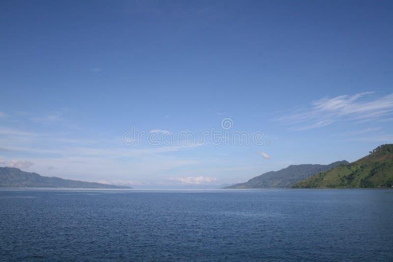 El cielo azul y el lago azul toba imágenes de archivo libres de regalías