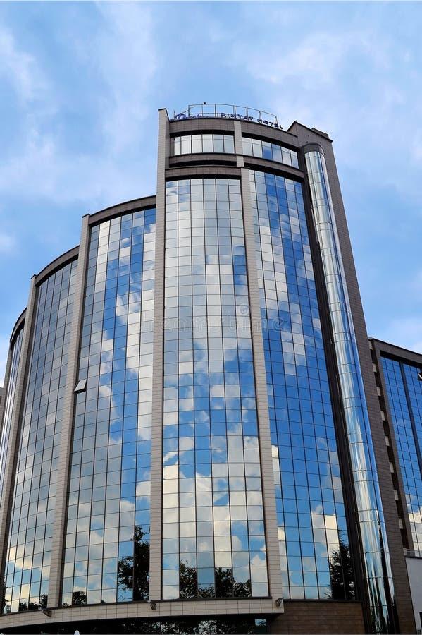 El cielo azul y las nubes se reflejan en las ventanas del espejo de un hotel moderno del vidrio y del hormigón, día soleado, visi fotografía de archivo