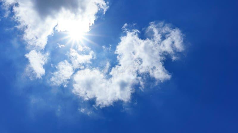 El cielo azul y el sol es brillantes detrás de la nube de cúmulo mullida fotos de archivo libres de regalías