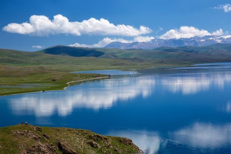 El cielo con las nubes hermosas reflejadas en la superficie de un lago de la montaña foto de archivo