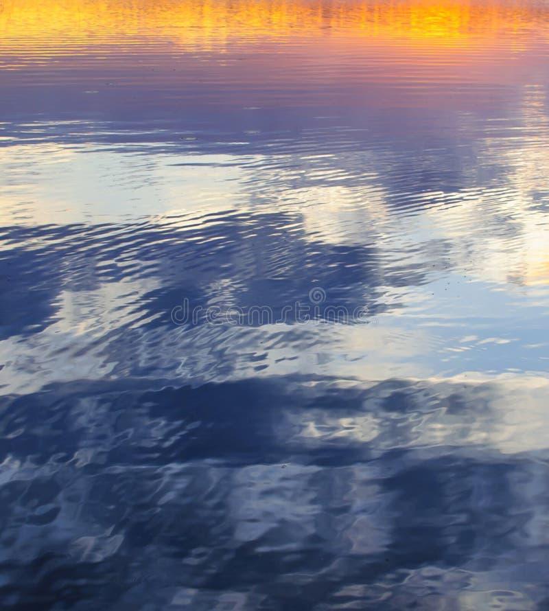 El cielo de la tarde colorea la reflexión en fondo del extracto del lago imagenes de archivo
