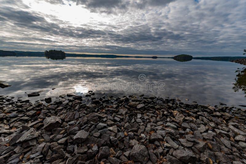El cielo gris refleja en agua tranquila en un lago foto de archivo