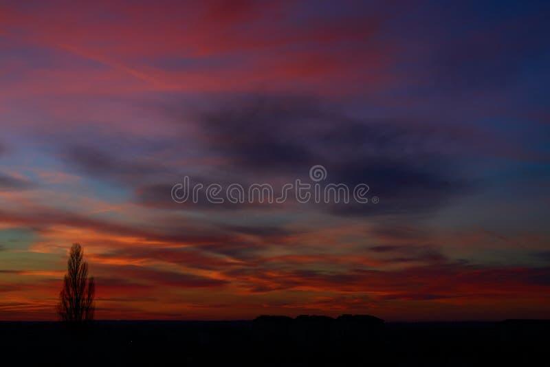 El cielo hermoso en la puesta del sol con original colorea tres casas y un árbol foto de archivo