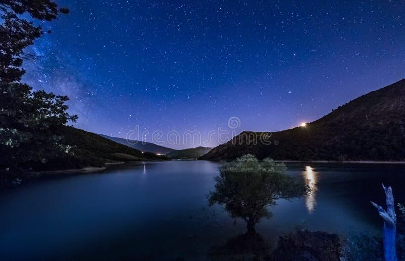 El cielo nocturno asombroso protagoniza paisaje del lago con la vía láctea imágenes de archivo libres de regalías