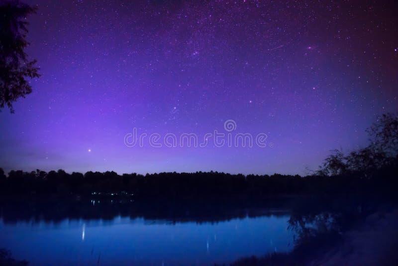 El cielo nocturno hermoso con muchos protagoniza en un lago imagen de archivo libre de regalías