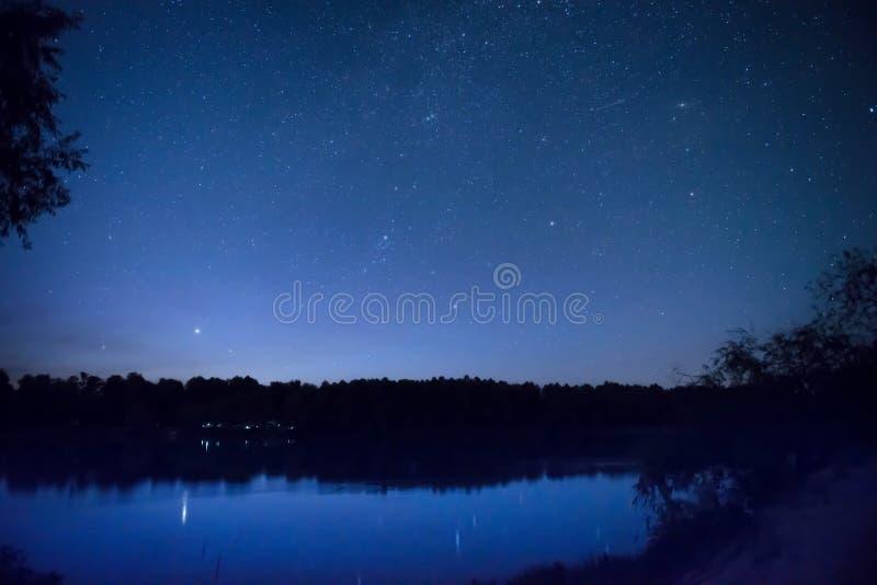El cielo nocturno hermoso con muchos protagoniza en un lago fotos de archivo libres de regalías