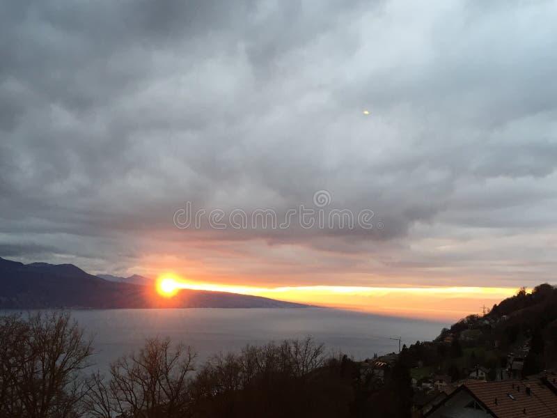 El cielo rojo de la puesta del sol se nubla el lago imagenes de archivo