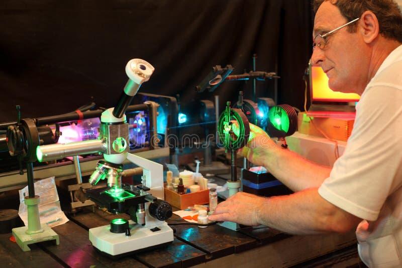 El científico con el vidrio demuestra el laser foto de archivo libre de regalías