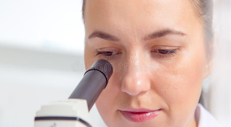 El científico de sexo femenino joven en el laboratorio, haciendo experimenta en laboratorio imagenes de archivo
