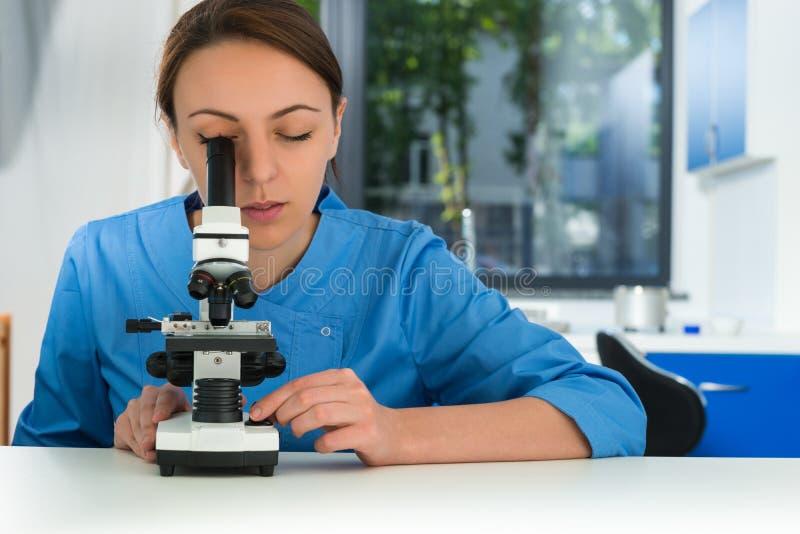 El científico de sexo femenino joven en uniforme está mirando a través de un microscop fotos de archivo