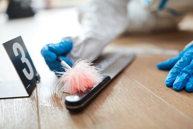 El científico forense busca la huella dactilar en el cuchillo foto de archivo