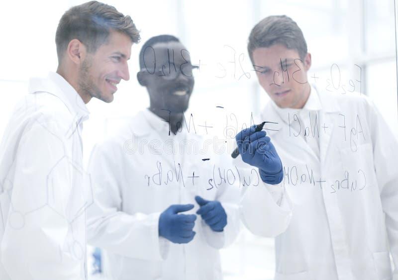 El científico prometedor hace notas en el tablero imagenes de archivo