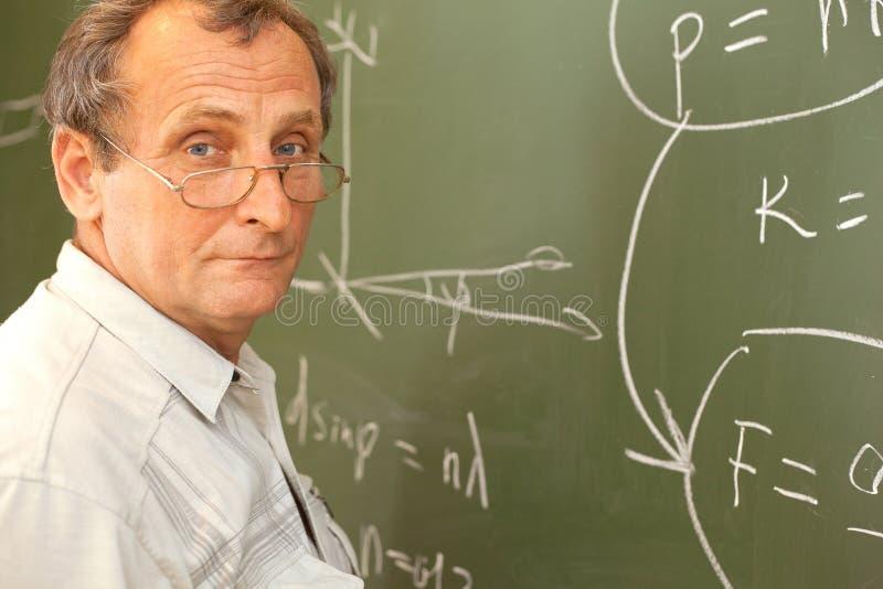 El científico soluciona la ecuación en la pizarra fotos de archivo