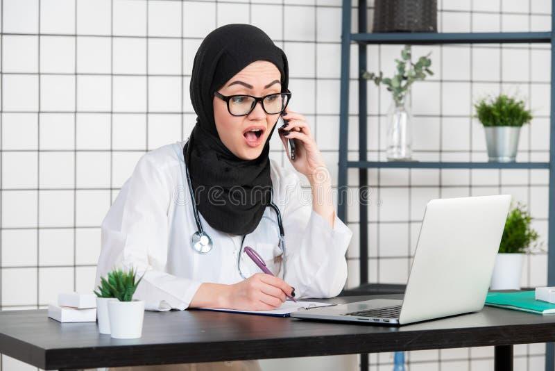 El científico velado de sexo femenino que se sienta en su escritorio que mira el ordenador portátil abre su boca con la emoción c foto de archivo
