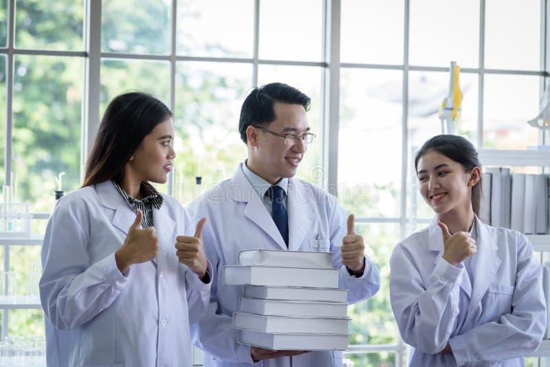 El cient?fico asi?tico mayor tiene asignaci?n de nuevo trabajo a los estudiantes en laboratorio con felicidad imagen de archivo