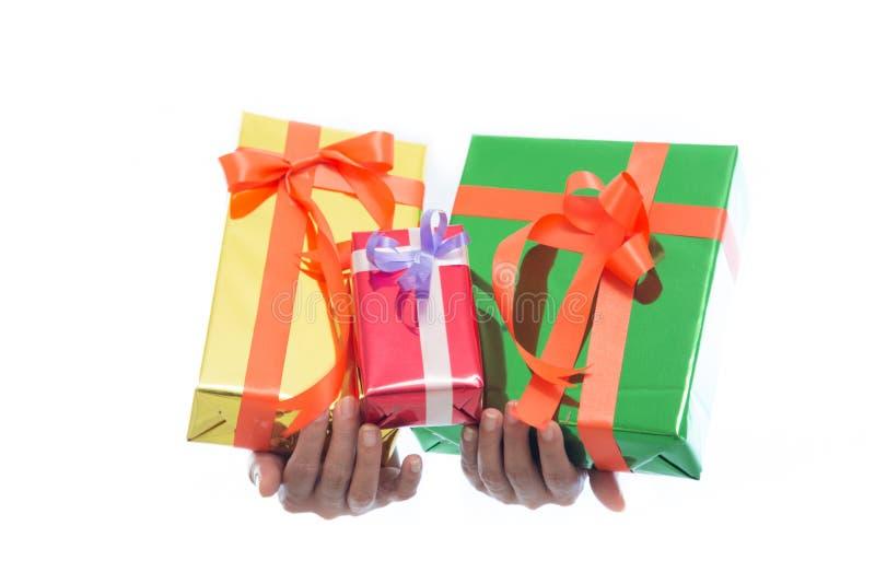 El cierre de manos detiene la caja de regalo verde aislada en el fondo blanco imagenes de archivo