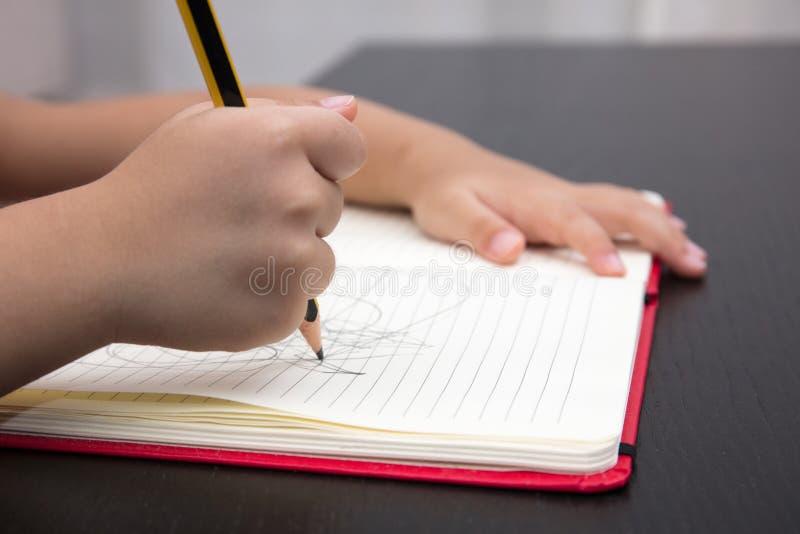 El cierre de niños da la escritura en el libro de ejercicio fotos de archivo libres de regalías