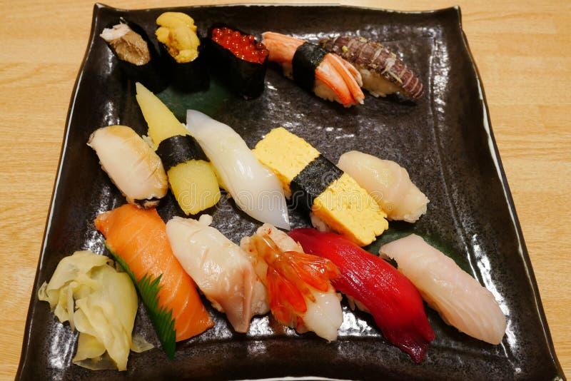 El cierre del sushi de lujo del sashimi instaló en la placa negra en el restaurante japonés de Otaru imagenes de archivo