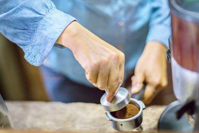 El cierre encima de Barista está presionando el café molido usando el pisón imágenes de archivo libres de regalías