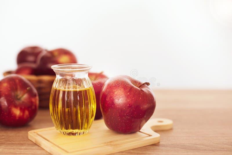 El cierre encima de la fruta y del jugo rojos del vinagre de sidra de manzana, ayudas de Apple pierde el peso y reduce la grasa d imagen de archivo