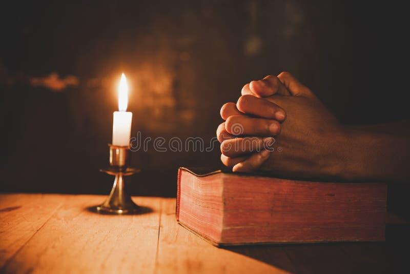 El cierre encima de la mano del hombre está rogando en la iglesia con la vela encendida fotos de archivo