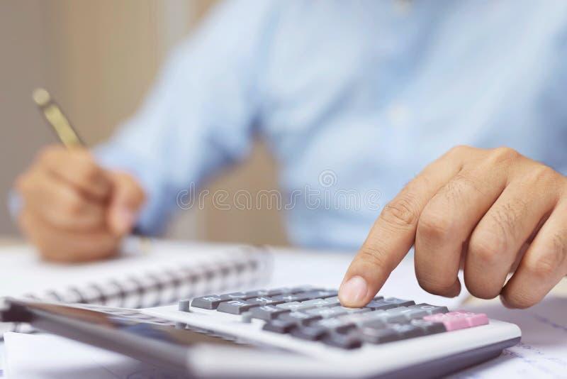 El cierre encima de la mano del hombre de negocios está escribiendo en un cuaderno y usando la calculadora que cuenta haciendo la foto de archivo libre de regalías