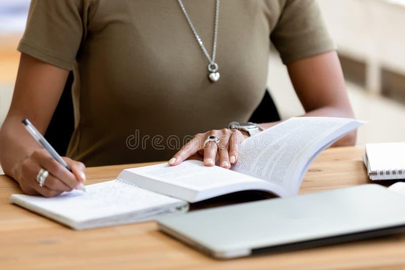 El cierre encima de la pluma de tenencia femenina africana de las manos hace notas fotografía de archivo libre de regalías
