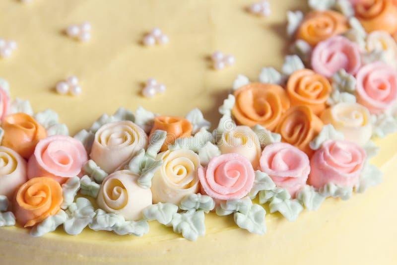 El cierre encima de las flores poner crema coloreadas pastel apelmaza la decoración fotografía de archivo