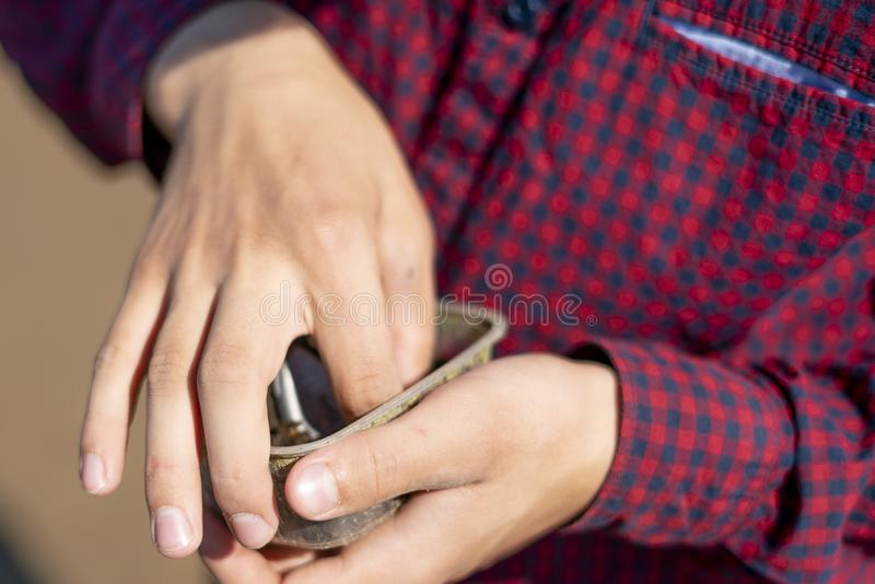El cierre encima de las manos toma cebo de pesca del gusano y lo puso en el cierre del gancho encima de a imagen de archivo libre de regalías