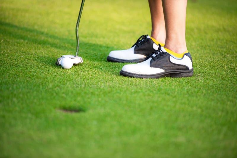 El cierre encima de las piernas del golfista se acerca a la pelota de golf que pone en el verde, imagen de archivo