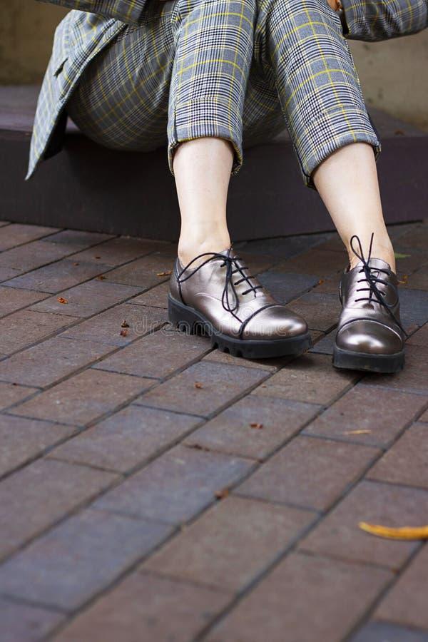 El cierre encima de las piernas de la mujer weared los pantalones acortados y las botas elegantes brillantes con los cordones en  imágenes de archivo libres de regalías