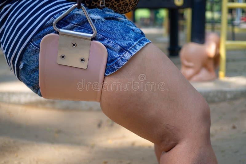 El cierre encima de los muslos regordetes de la mujer de la pierna está llevando los vaqueros cortos que se sientan en sillas de  imágenes de archivo libres de regalías