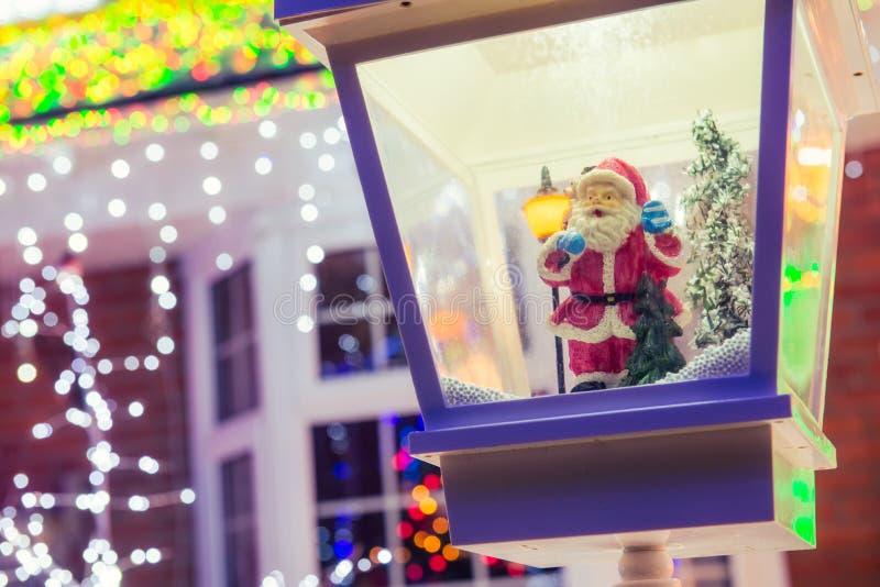 El cierre encima de Santa Claus en linterna decorativa en la nieve en la Navidad borrosa enciende el fondo y decoraciones al aire imágenes de archivo libres de regalías