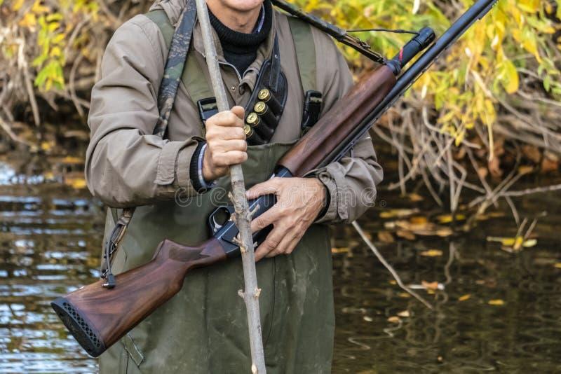 El cierre encima del cazador masculino lleva el rifle que camina en el lanscape f de la naturaleza foto de archivo