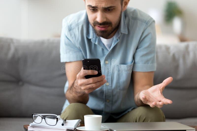 El cierre encima del hombre confuso que tiene problema con el teléfono, recibe malas noticias fotos de archivo libres de regalías