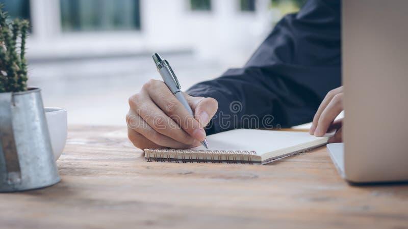 El cierre encima del hombre de negocios escribe el cuaderno y ordenador portátil con imagen de archivo