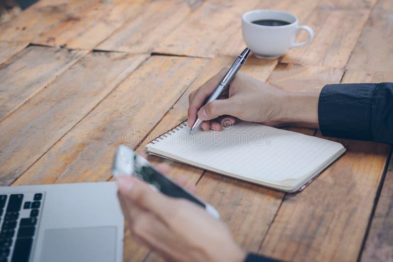 El cierre encima del hombre de negocios escribe el cuaderno y usar el teléfono celular foto de archivo