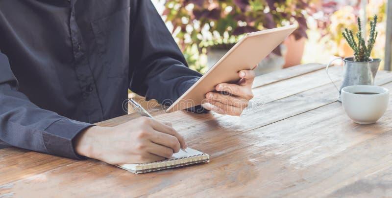 El cierre encima del hombre de negocios escribe en el cuaderno y usar el funcionamiento de la tableta imágenes de archivo libres de regalías