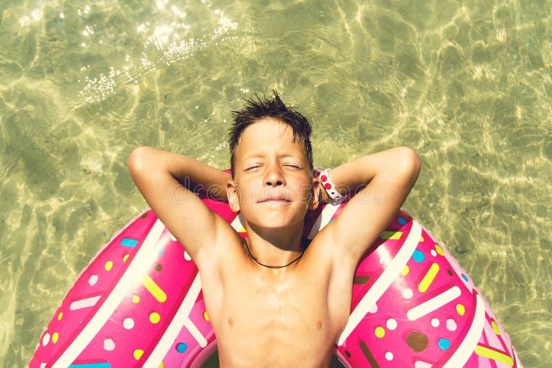 El cierre encima del portreit del muchacho está flotando en un anillo inflable del buñuelo en el mar Foto entonada imagen de archivo libre de regalías