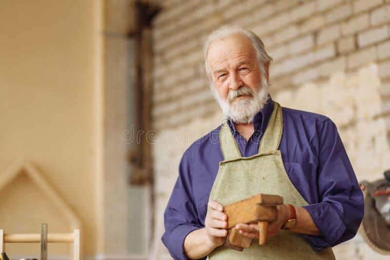El cierre encima del retrato del viejo ` masculino t del doesn sabe trabajar con el avión de madera fotos de archivo libres de regalías