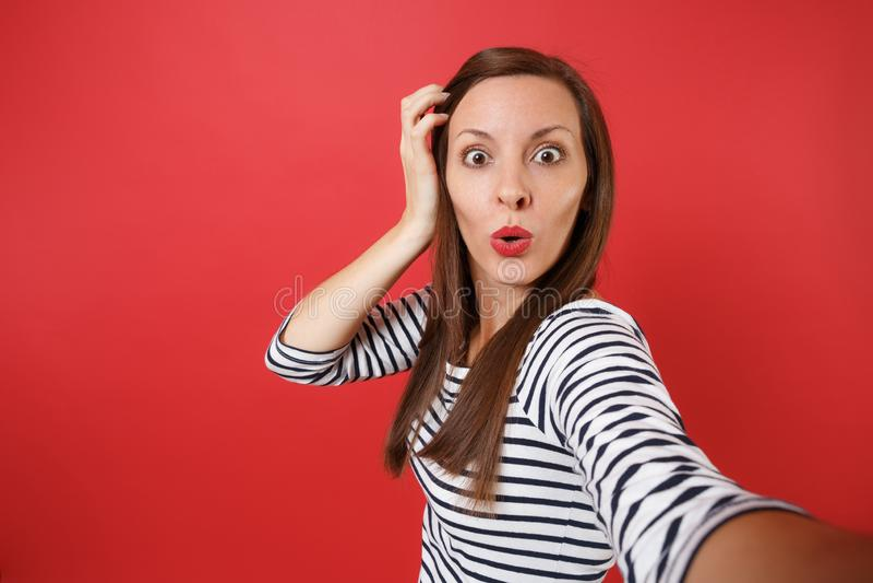 El cierre encima del selfie tirado de mujer joven chocada en la ropa rayada que guardaba la mano cerca de la cabeza, mirando sorp fotografía de archivo
