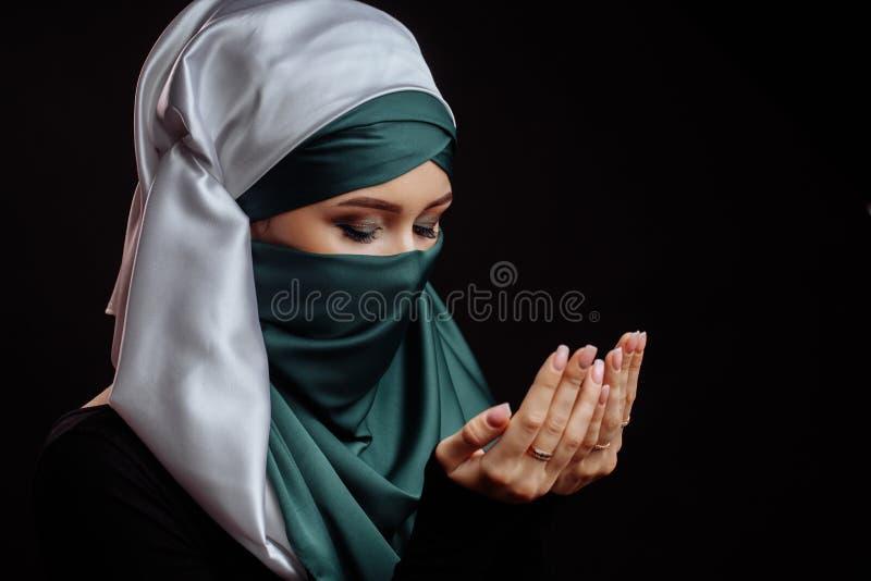 El cierre encima del tiro de la vista lateral de la mujer islámica con los ojos cerrados ha convertido al Islam foto de archivo libre de regalías