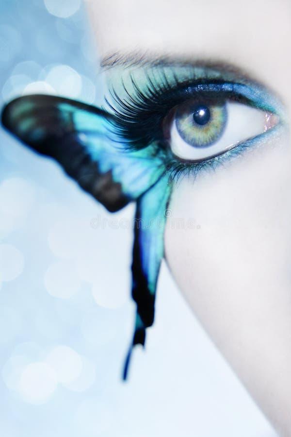 El cierre hermoso del ojo de la mujer para arriba con la mariposa se va volando fotografía de archivo libre de regalías