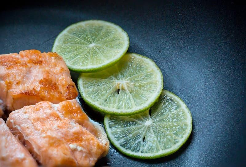 El cierre para arriba asó a la parrilla el filete de color salmón en la cacerola negra con 3 rebanadas del limón fotografía de archivo libre de regalías