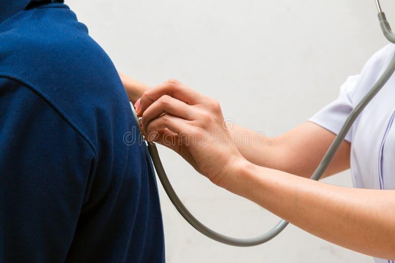 El cierre para arriba de la enfermera asiática escucha el patient& mayor x27; sonido de la respiración de s imagenes de archivo