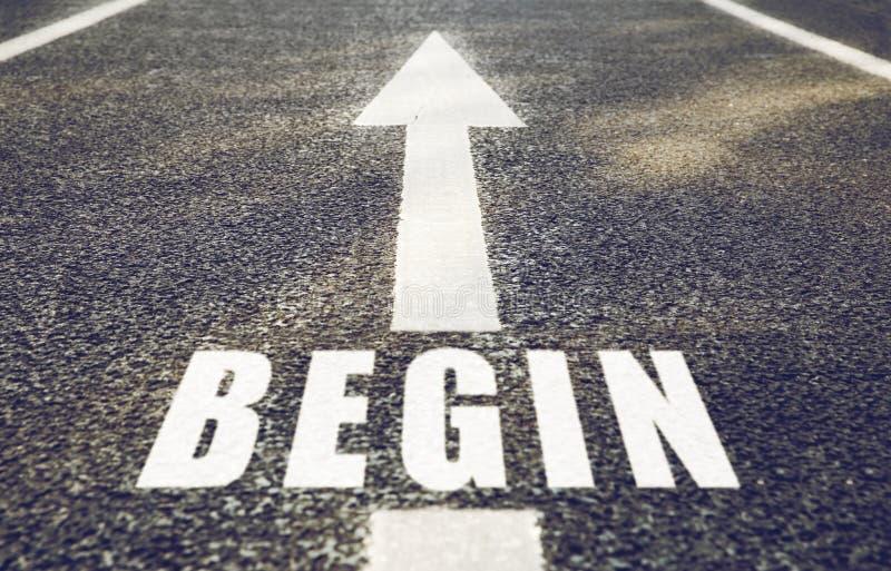 El cierre para arriba de la flecha y la palabra comienzan por la carretera de asfalto imagen de archivo