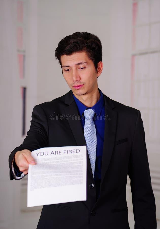 El cierre para arriba del hombre de negocios joven triste que lleva un traje y que sostiene una hoja de papel que consigue del je imagenes de archivo